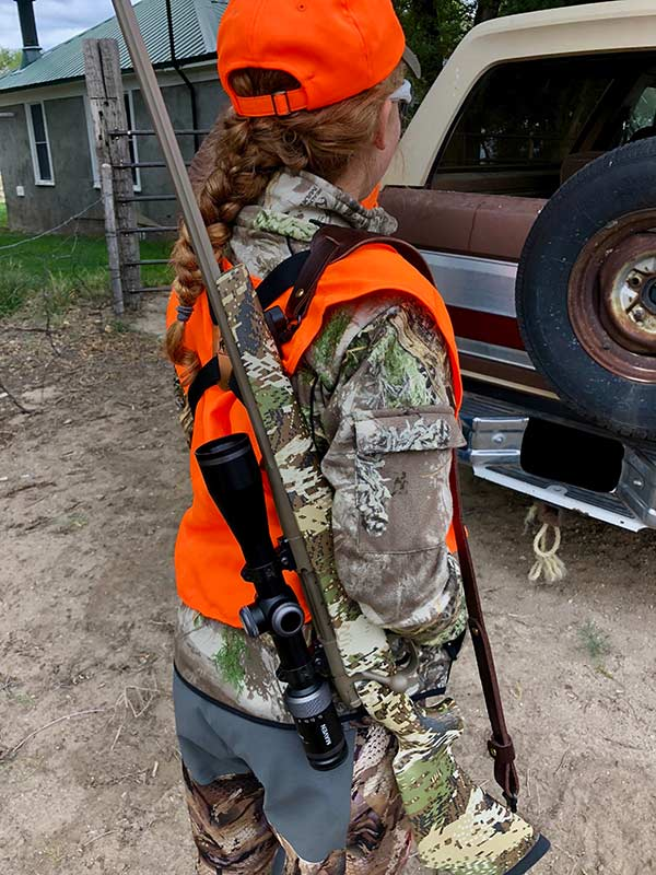 rifle in a sling over woman's shoulder