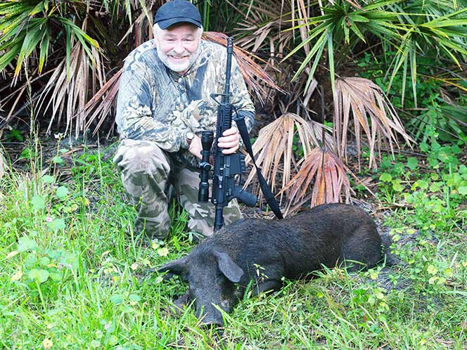 The author and a hog he shot in Florida with a DPMS in .308 Winchester.