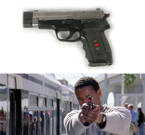 A photo of the actual screen used pistol (top) and Barnes aiming the gun with the laser sight activated.