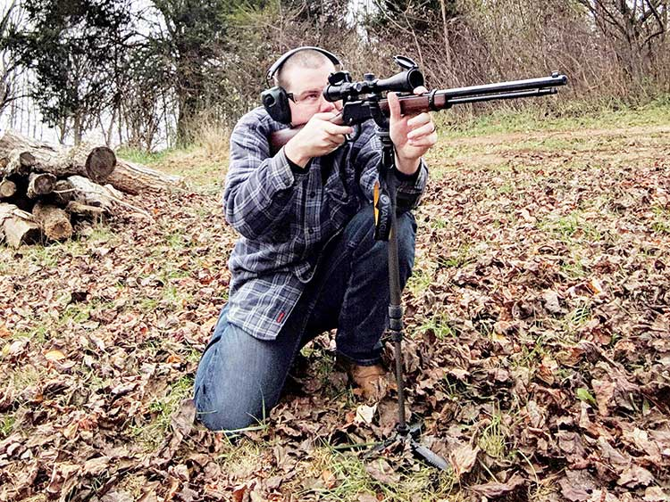 man using shooting sticks while aiming rifle