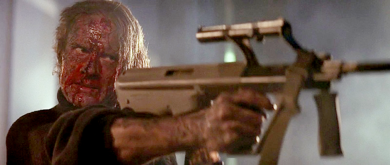 Karl (Alexander Godunov) holding his Steyr AUG bullpup rifle one handed in the final sequence.