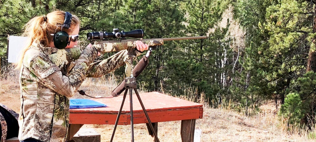 A woman aiming a rifle in the woods.