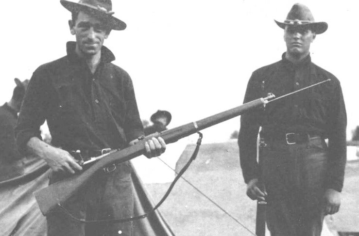 two soldiers holding bayonet rifles