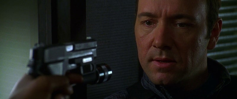 Garfield holds one of the HRT Team's SIG P226 pistols on Spacey.
