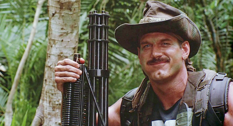 Blain (Jesse Ventura) in the shot used for the final credits, posing with Ol' Painless.