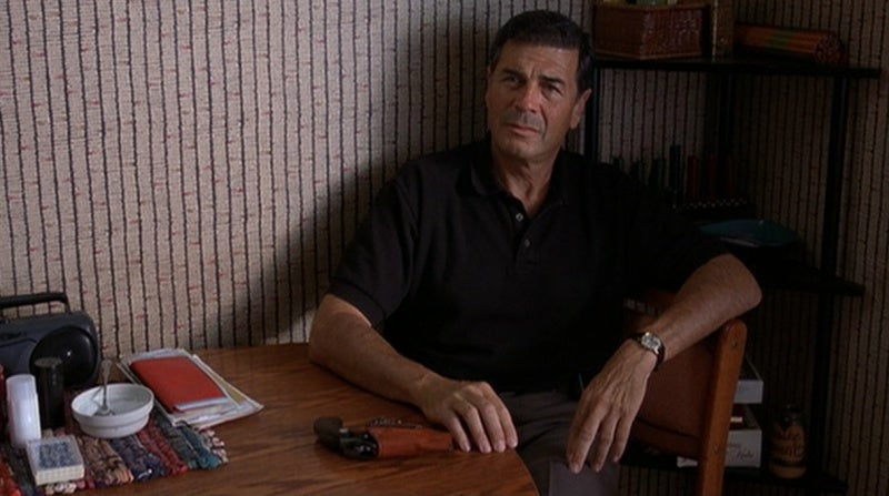 Max at the table in Jackie's apartment with his holstered Colt Detective Special.
