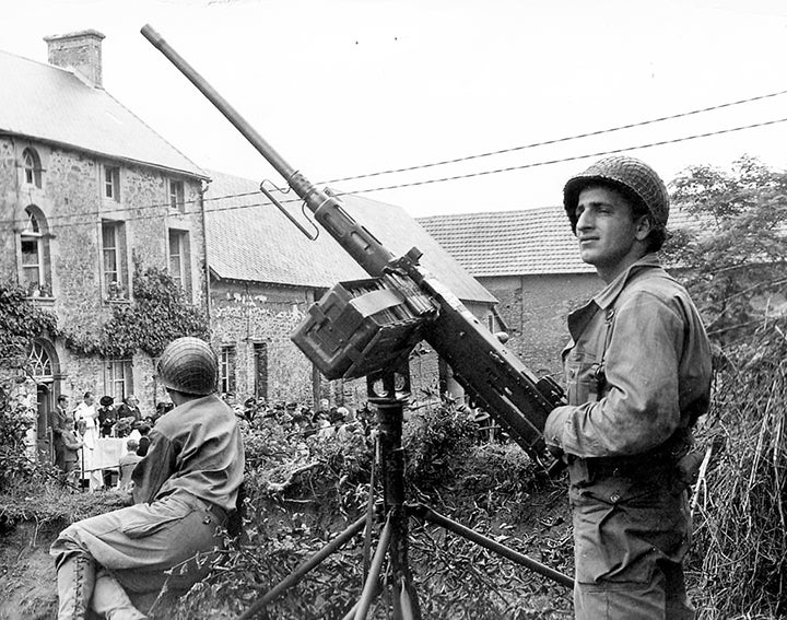 A U.S. soldier in Normandy stands guard with the M2HB installed on a dual-purpose mounting.