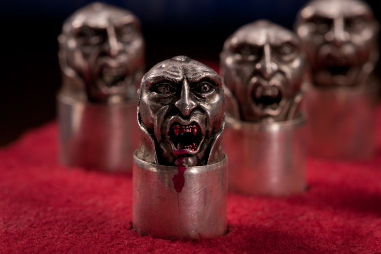 Each silver bullet is shaped into the face of a vampire-killing demon.