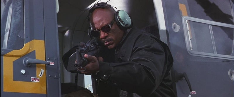 Luther (Ving Rhames) fires a Colt 9mm Submachine Gun from a helicopter.