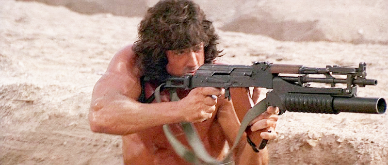 Note how Stallone has to awkwardly grip the AKM's magazine in order to fire the M203 grenade launcher.