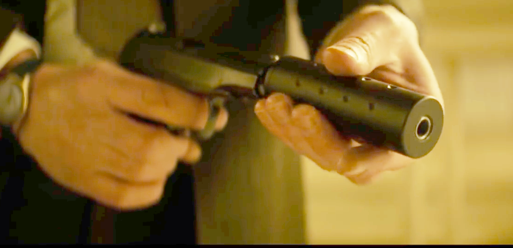 Lorraine threads a suppressor onto her Makarov before the hotel room shootout.