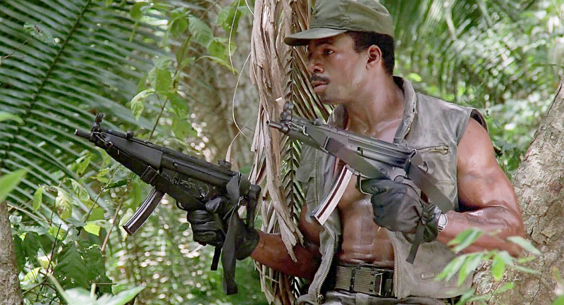 Dillon (Carl Weathers) with two mocked-up MP5A3 submachine guns.