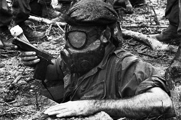 A tunnel rat emerging from an opening with an M1911A1, a flashlight, and a gas mask. The duty was one of the most dangerous in the war and had a high mortality rate.