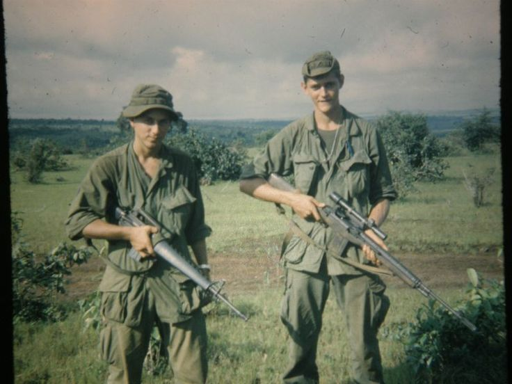 Two U.S. soldiers in Vietnam, the left with an M16A1 and the other with a scoped M14 rifle.