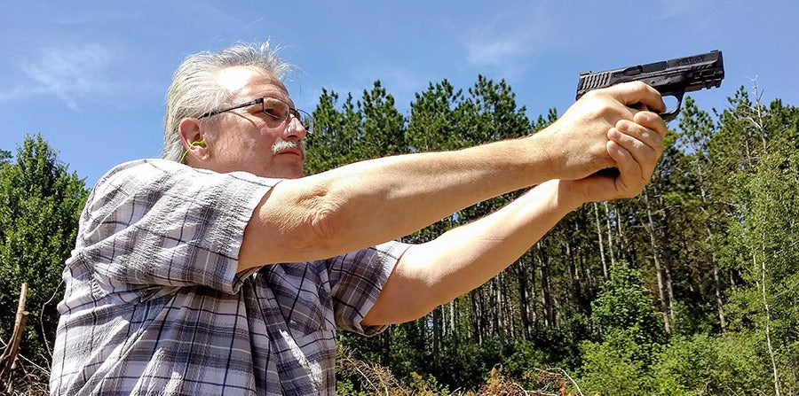 man aiming smith and wesson handgun