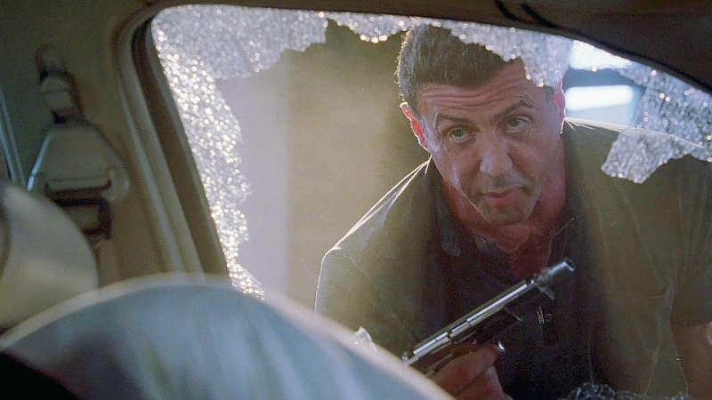 Stallone as Jimmy with his Browning Hi-Power fitted with a 3-lug adapter for a quick-release suppressor.