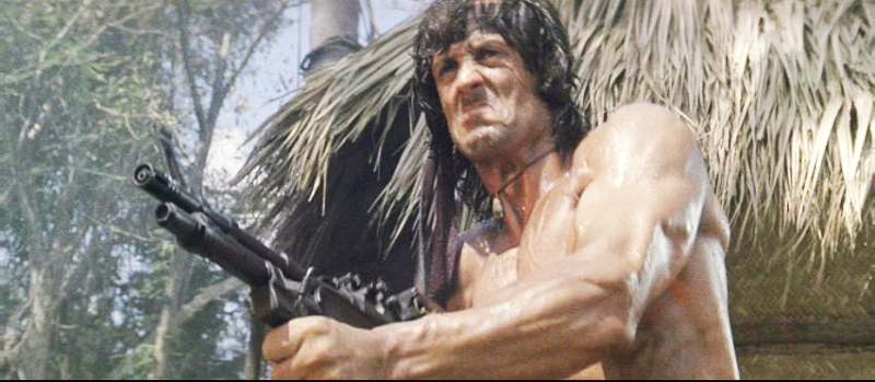 Rambo using the M60E3 to clear out the enemy camp before freeing the POWs.