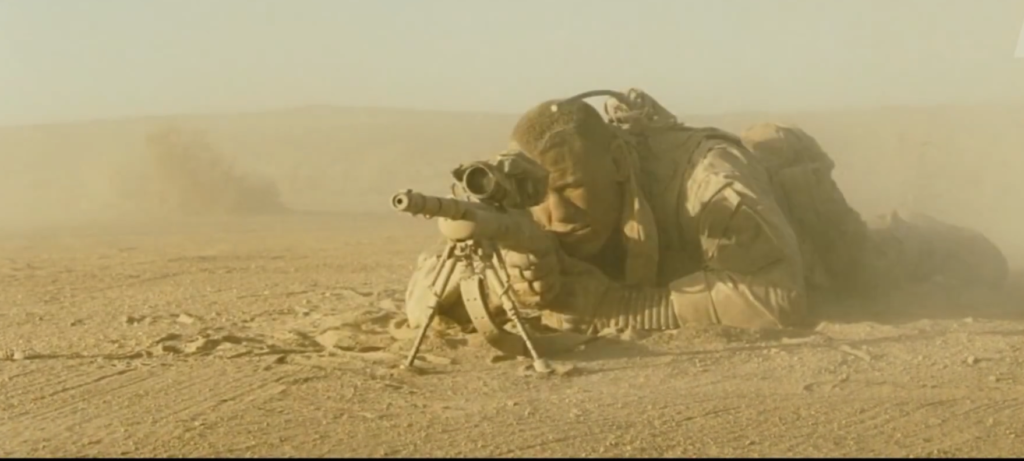 Matthews aiming his M24 through a swirl of wind and dust.