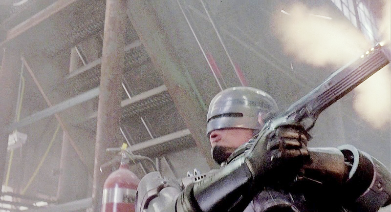 RoboCop fires a no-look shot with his Auto 9 that his targeting system has already locked during the drug warehouse shootout scene.