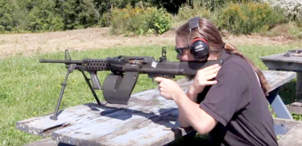 Firing a Colt CMG-3. Note the device anchored in the mag well holding the ammo belt.