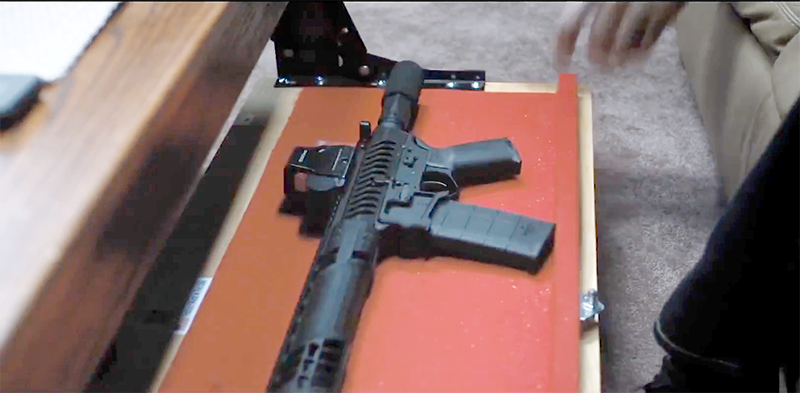 In the trailer, we see Kersey keeps an AR with no stock hidden in a compartment in a coffee table.