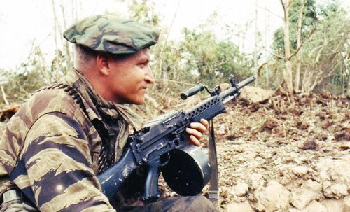 A Navy SEAL keeps his Stoner 63 light machine gun at the ready while the rest of his squad prepares demolition charges on a Vietcong bunker. The weapon is fitted with a 150-round drum belt container.