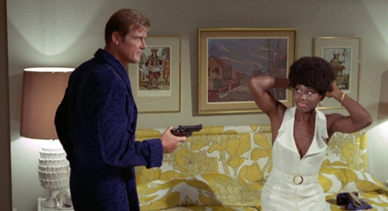 Bond, after disarming Rosie, holds her gun on her while she fixes her wig.