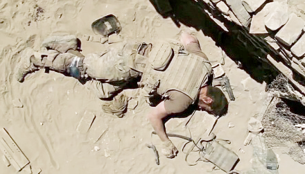 Isaac with an M9 pistol by his head on the ground.
