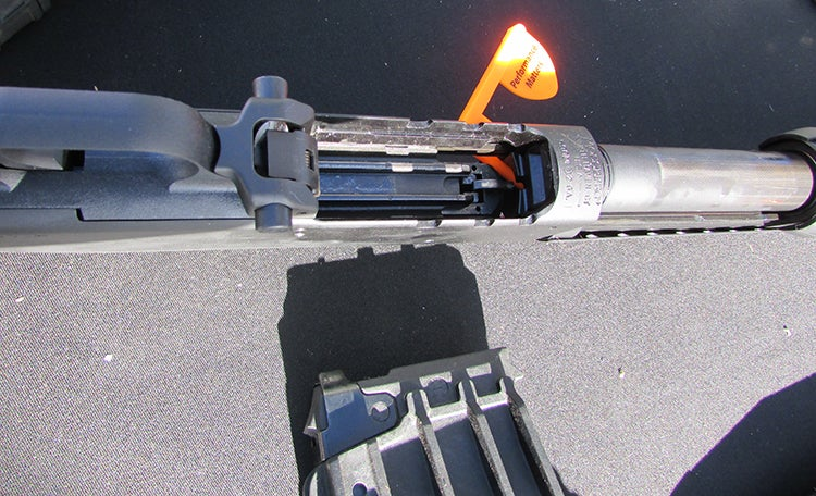 The ambidextrous magazine release on the 590M is located just in front of the trigger guard.