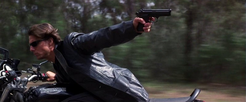 Hunt fires his Beretta 92FS Brigadier behind him, aiming with the side mirror on the moving motorcycle, and actually hits something.