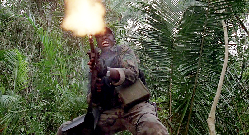 Mac firing his M60 at the fleeing, camouflaged Predator after Blain is killed. You can see the ammo can hanging from his shoulder.