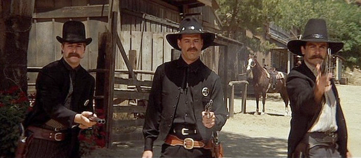 Bruce Willis plays early western film star Tom Mix, who is playing Wyatt Earp in a movie within the movie.