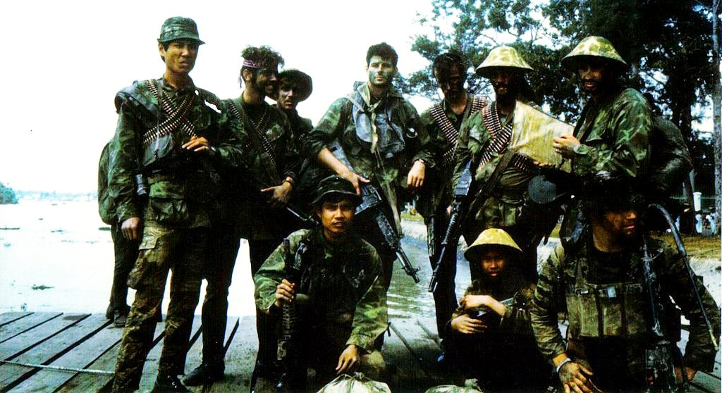 Navy SEALs pose for a photo somewhere in Vietnam, 1970. The SEAL in the center of the group is carrying a Stoner 63A1 Mk 23 Mod 0 Commando.