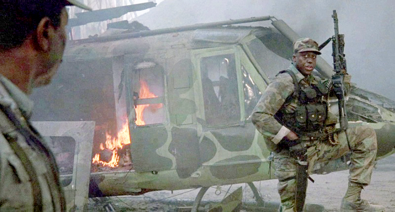 Mac (Bill Duke) resting near a destroyed helicopter after the raid at the jungle base.
