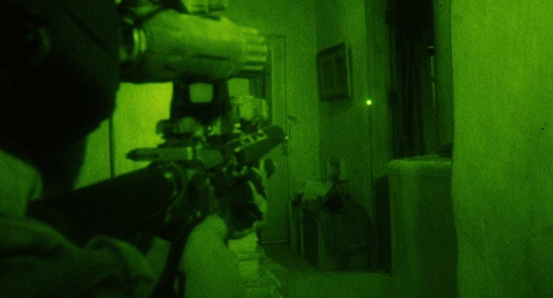 A still of the moment before the Navy SEAL takes the fateful shot on Bin Laden with his HK416 in the film *Zero Dark Thirty*.