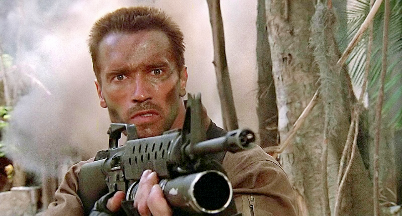 Dutch (Schwarzenegger) aiming his AR-15 with a faux M203 grenade launcher mounted under the barrel.