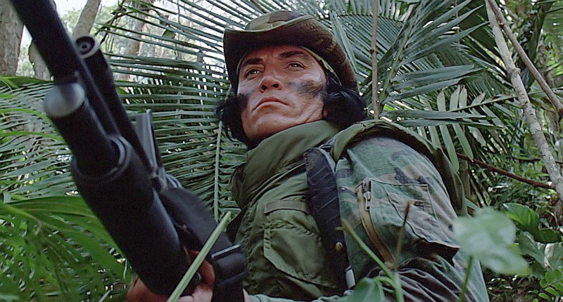 Billy (Sonny Landham) pushing through the jungle with his AR-15 with an underslung Mossberg 500 pump-action shotgun.
