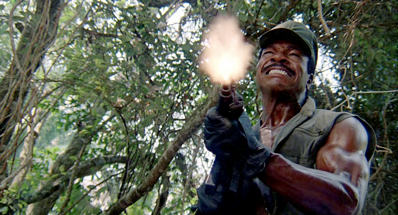 Dillon firing one of his MP5A3s just before he is hit by one of the Predator's energy blasts.