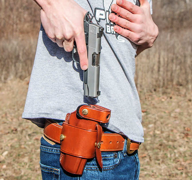 Now you can start movement toward the holster. Place your support hand on your chest—out of the way—and rotate the muzzle 90 degrees, so that it is pointing toward the ground. Remember to keep your fi