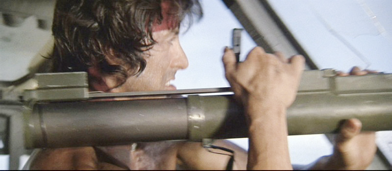 Rambo readies to fire the M72 LAW rocket launcher with his hand on the trigger, located on top of the tube.