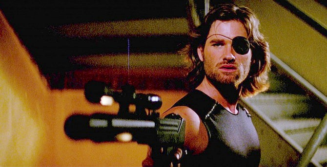 Snake Plissken (Russell) with his MAC-10 fitted with a scope mounted on a long suppressor.
