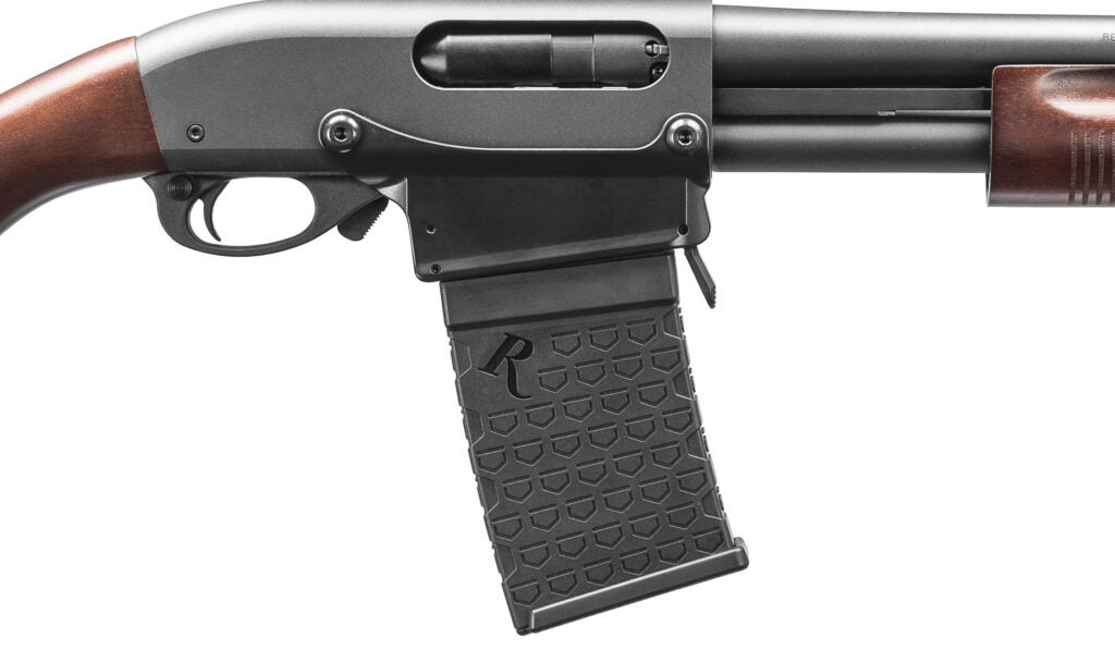 A closeup of the 870 DM's magwell, magazine, and controls. The magazine release lever is located in front of the magwell.