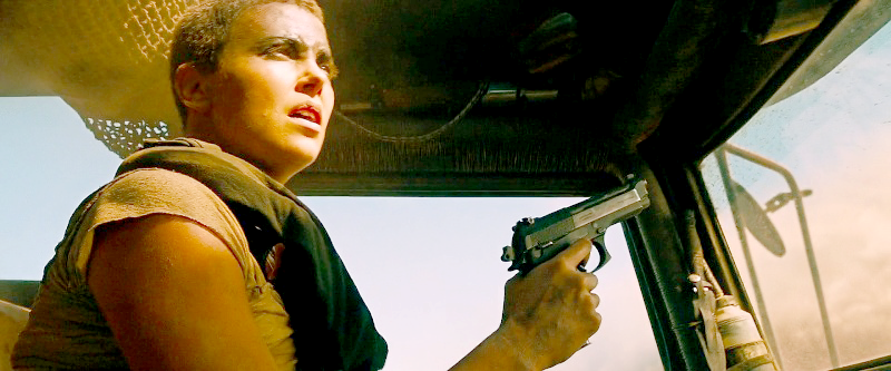 Furiosa with her Taurus looking toward the oncoming sandstorm.