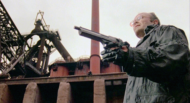 Boddicker in a later scene with the same Mark I. Note the extended barrel with visible threads for attaching the suppressor.