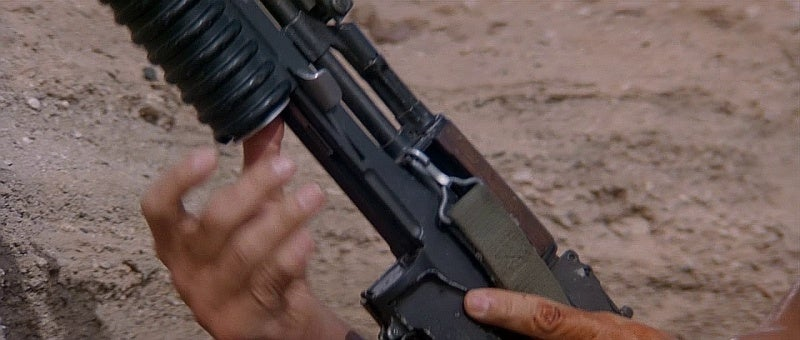 Here Stallone awkwardly hits the release on the M203 with his left index finger to reload it.