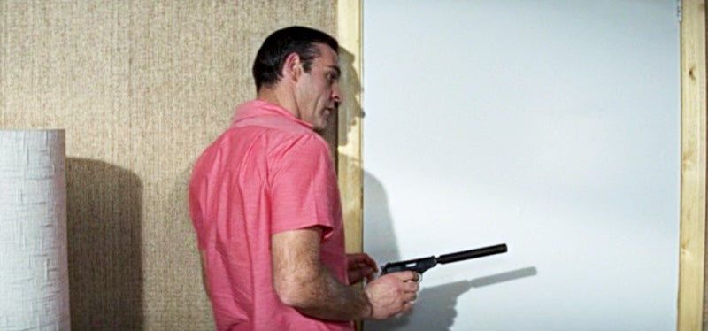 Bond approaches a door with his suppressed Walther PPK.