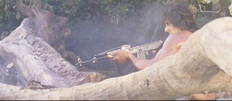 Rambo fires his AKM at enemy soldiers after they fatally shoot his companion, Co Bao.