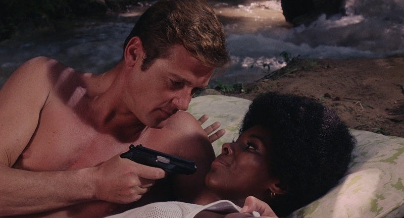 Bond (Roger Moore) interrogates Rosie with his Walther PPK