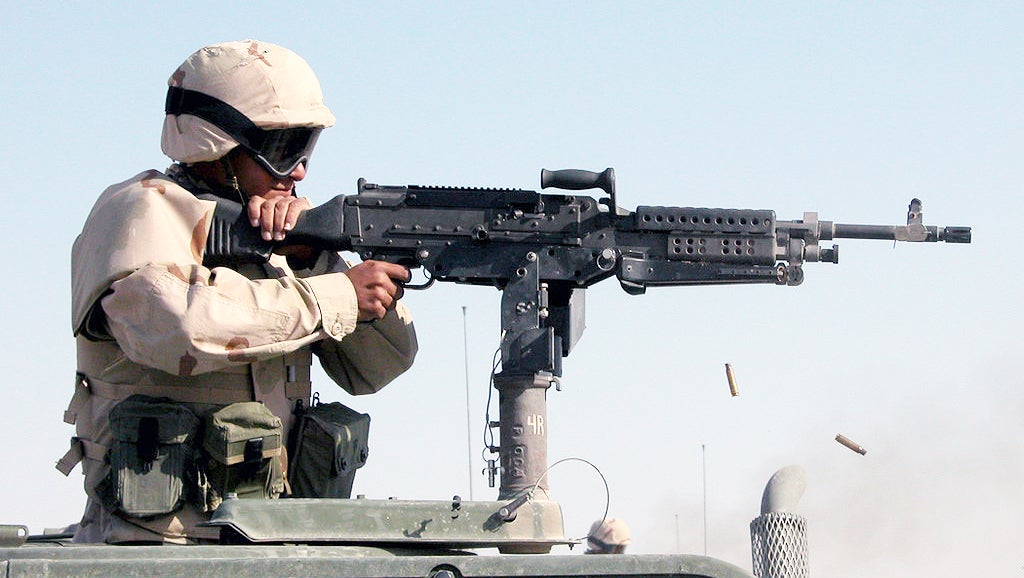 A Seabee fires an M240B mounted atop a Humvee.