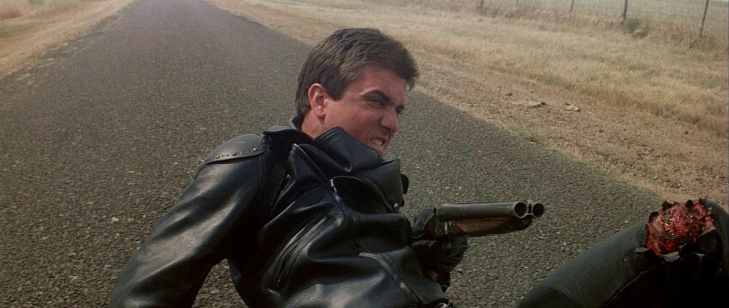 Gibson as Max Rockatansky in the original *Mad Max* with his signature sawed-off double-barrel shotgun, and a mangled knee.